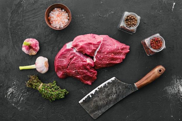 Raw fresh beef chuck eye roast on black