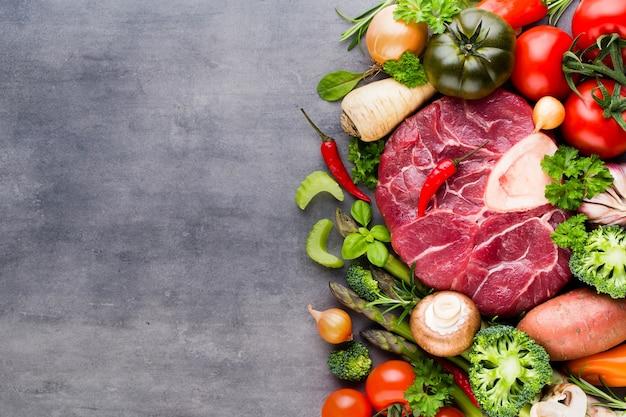 Стейк рибай сырого свежего мяса говядины со специями и ингредиентами.