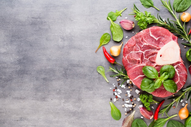 Raw fresh beef meat ribeye steak with spice and ingredients.