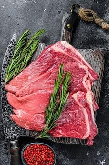Стейк из сырого свежего мяса говядины с зеленью и специями. черный фон. вид сверху.