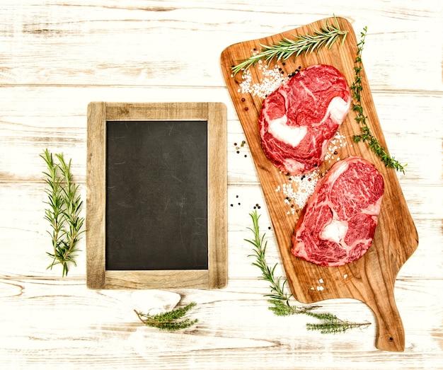 나무 책상에 허브, 향신료, 칠판을 넣은 신선한 생 쇠고기. 음식 배경입니다. 빈티지 스타일 톤 그림