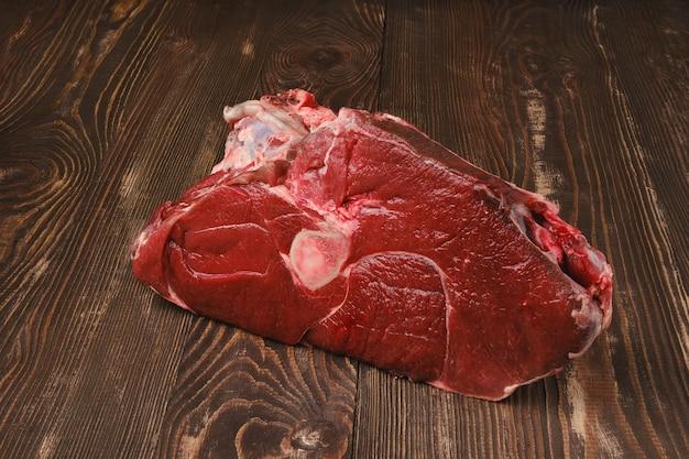 원시 신선한 쇠고기 정강이 나무 배경에 크로스 컷