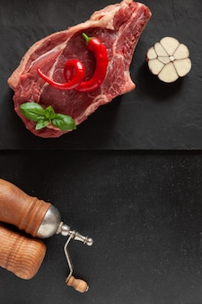 Raw fresh beef steak with bone, spices and seasonings on stone cutting board.