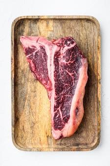Сырой свежий говяжий стейк на косточке дриа, выдержанный на деревянном подносе, на белом каменном фоне, плоский вид сверху