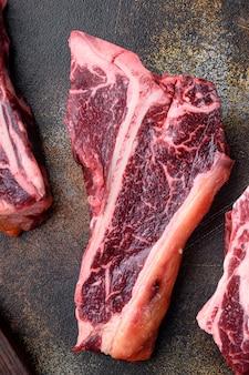 Набор сырых свежих говяжьих стейков на косточке, на старом темном деревенском фоне, плоский вид сверху