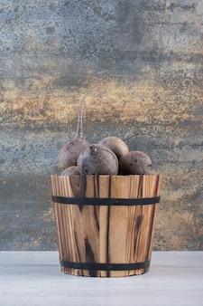 Barbabietole fresche crude nel secchio di legno. foto di alta qualità