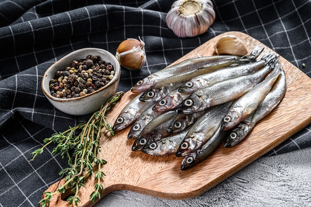 Raw fresh capelin fish on cutting board