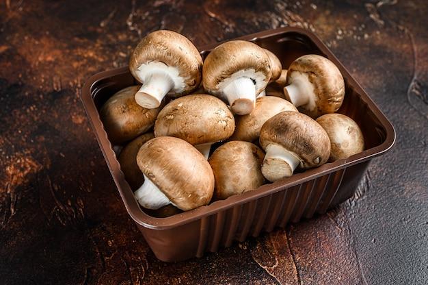 Сырые свежие грибы шампиньоны в пластиковой коробке.