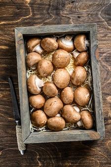 Сырые свежие грибы шампиньоны в деревянном ящике. темный фон. вид сверху.