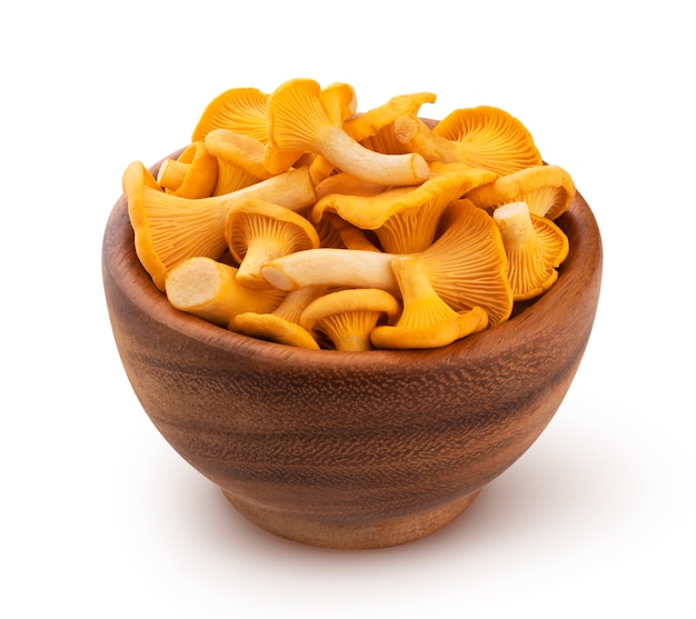 Raw fresh chanterelle mushrooms in wooden bowl isolated on white with clipping path