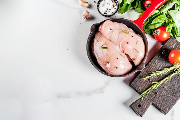 Raw fresh chicken breast fillet with herbs and spices for cooking, in iron cast skillet, white marble table, copy space top view