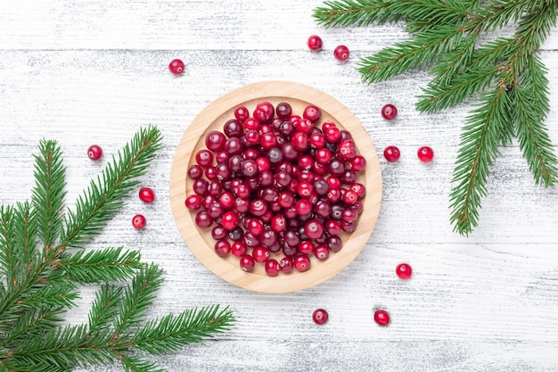 Raw fresh cranberries in wooden bowl and fir branches on light wood background. top view - image