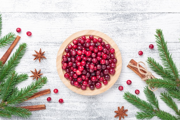 Raw fresh cranberries in wooden bowl, spice and fir branches on light wood background. top view - image