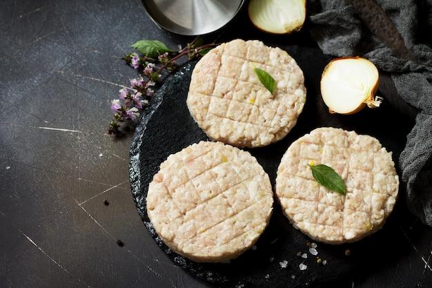 ブラックボードにスパイスを使って調理する自家製ハンバーガー用の牛肉からの生の新鮮なカレットバーガー