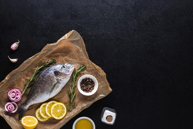 Сырая свежая рыба дорадо на кулинарной бумаге, подготовленной для приготовления пищи со специями на черном фоне. морепродукты. вид сверху. скопируйте пространство.