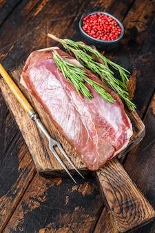 Стейк из сырого свежего филе утиной грудки с травами и розмарином. темный деревянный стол. вид сверху.