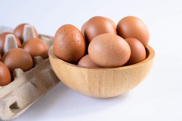 Сырые свежие яйца в миске и в картонной коробке
