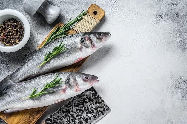 生の新鮮な魚のシーバスと調理用の材料。白色の背景。上面図。スペースをコピーします。