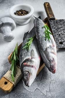 生の新鮮な魚のシーバスと調理用の材料。白色の背景。上面図。