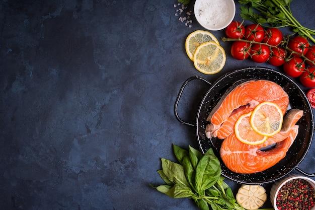 Сырая свежая рыба с овощами готова к приготовлению. сырой стейк из лосося с лимоном и специями на сковороде.