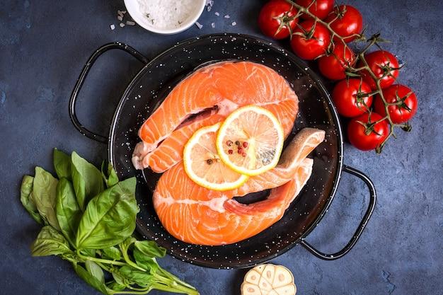 Сырая свежая рыба с овощами готова к приготовлению. сырые стейки из лосося с лимоном, специями и зеленью на сковороде.