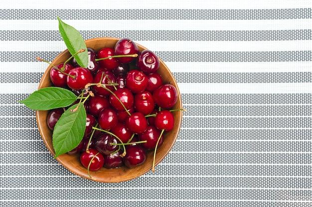 Raw fresh garden cherry in wooden bowl
