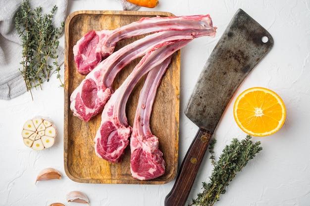 Набор сырых свежих отбивных из корейки ягненка с ингредиентами, морковью, апельсином, зеленью и старым мясным ножом, на белом каменном столе, вид сверху