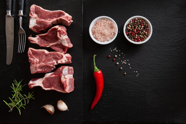 Raw fresh lamb meat ribs and seasonings on black stone background