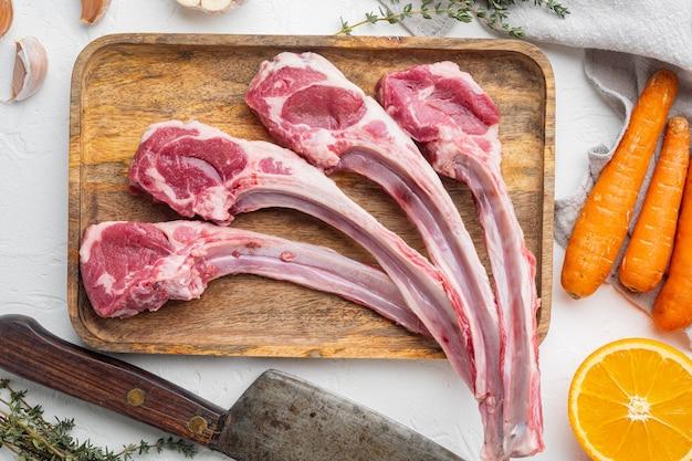 Сырые свежие ребра ягненка, готовые для приготовления, с ингредиентами, морковью, апельсином, зеленью и старым мясным ножом, на белом каменном столе, плоская планировка, вид сверху