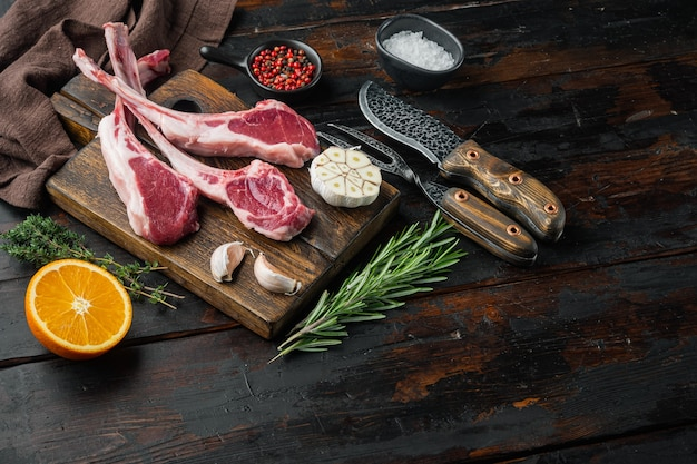 Сырые свежие ребра ягненка, готовые для приготовления, с ингредиентами, морковью, апельсином, зеленью, на старом темном деревянном столе Premium Фотографии