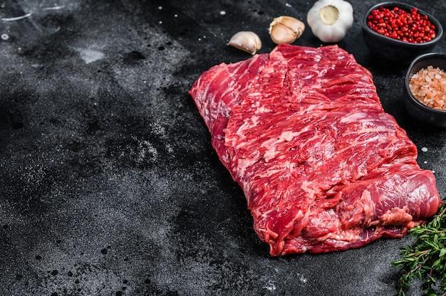 허브와 함께 원시 신선한 대리석 쇠고기 양지머리 고기. 검은 배경. 평면도. 공간을 복사합니다.