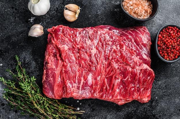 허브와 함께 원시 신선한 대리석 쇠고기 양지머리 고기. 검은 배경. 평면도.