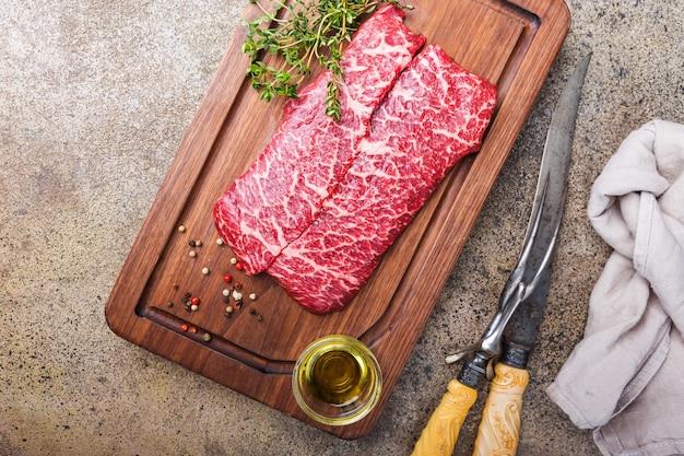 돌 표면 위에 커팅 보드에 원시 신선한 대리석 고기 쇠고기 스테이크와 조미료, 평면도