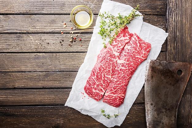 나무 표면 위에 종이에 원시 신선한 대리석 고기 쇠고기 스테이크와 조미료