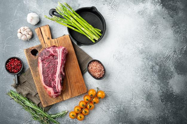 Сырое свежее мраморное мясо клубный стейк черного ангуса и набор ингредиентов, на сером каменном фоне, плоская планировка, вид сверху, с местом для текста