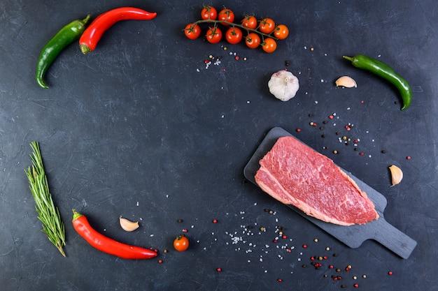 Raw fresh marbled meat and seasonings on dark background top vie