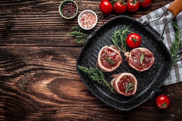 Сырое свежее мраморное мясо стейк из филе миньон. медальон стейки, завернутые в бекон на темном бетонном фоне. вертикальное изображение, место для текста.