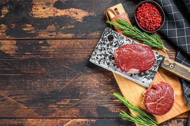 Сырое свежее мраморное мясо стейк из филе миньон на разделочной доске. темный деревянный фон. вид сверху. скопируйте пространство.