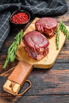 Сырое свежее мраморное мясо стейк из филе миньон на разделочной доске. темный деревянный фон. вид сверху.