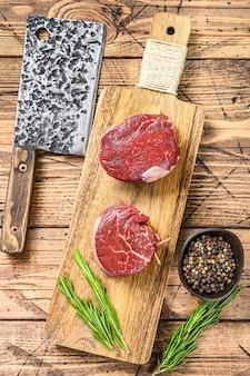 Сырое свежее мраморное мясо стейк из филе миньон. деревянный фон. вид сверху.