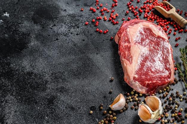 生の霜降り肉ステーキリブアイ。食材を使ったブラックアンガスリブアイ。上面図。コピースペース