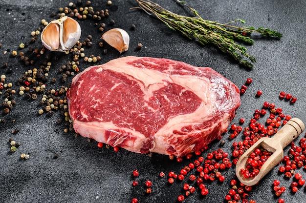 Сырое свежее мраморное мясо стейк рибай. рибай блэк ангус с кулинарными ингредиентами