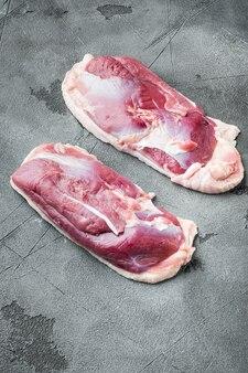 生の新鮮な肉、鴨胸肉の切り身セット、灰色の石のテーブル