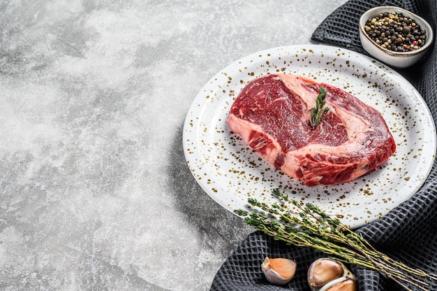 Raw fresh meat ribeye steak with seasoning on cutting board. rib eye beef steak. top view. copy space