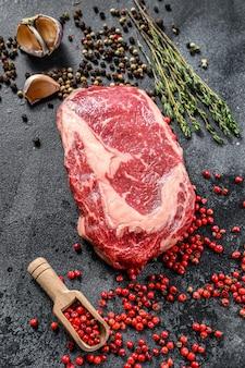 Сырое свежее мясо рибай стейк с приправой. рибай стейк из говядины. черный фон. вид сверху
