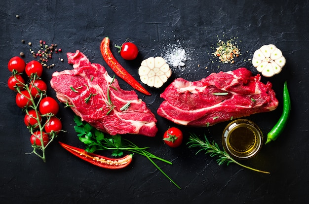 Raw fresh meat steak with cherry tomatoes, hot pepper, garlic, oil and herbs