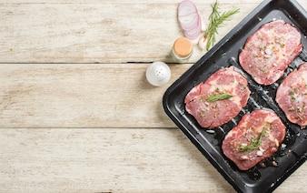 ローズマリーの葉と塩を使った生の新鮮な肉のステーキ、黒いトレイに調理する準備ができて、トップビュー