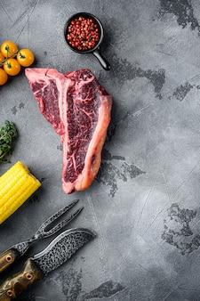 Стейк на косточке из сырого свежего мяса со специями, чесноком и розмарином, на сером каменном фоне, плоская планировка, вид сверху, с местом для текста