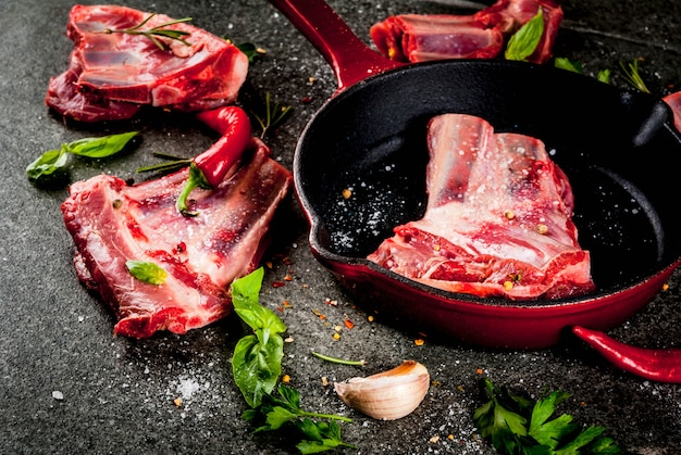 Raw fresh meat, uncooked lamb or beef ribs with hot pepper, garlic and spices with frying pan skillet on dark stone , copyspace