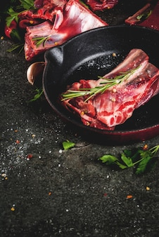 Raw fresh meat, uncooked lamb or beef ribs with hot pepper, garlic and spices with frying pan skillet on dark stone ,